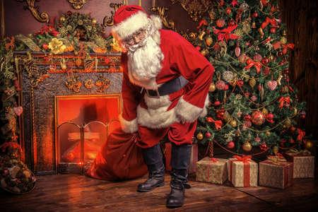 Babbo Natale porta il sacco con i regali per Natale. La casa è splendidamente decorata per Natale. Archivio Fotografico