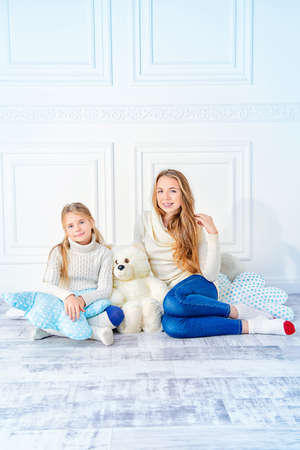Family portrait. Two cute girls, older and younger sister sitting together. Children's fashion, winter style.