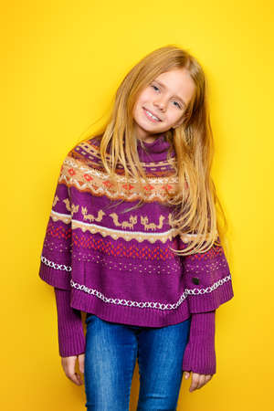 Kid's fashion. Portrait of a cute 7 year old girl wearing knitted clothes posing over bright yellow background. Autumn, winter fashion. Happy child girl. 写真素材