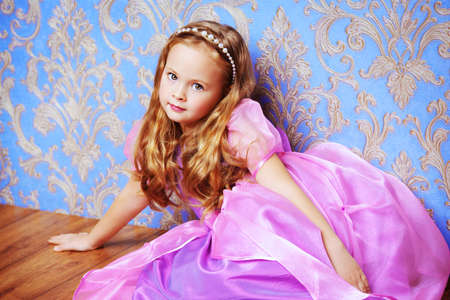 Pretty little girl in beautiful luxurious dress over vintage background. Kid's fashion. 免版税图像