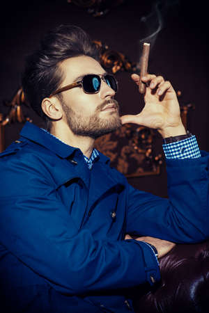 Portrait of a well-dressed imposing man in sunglasses standing in apartments with luxurious classic interior. Men's beauty, fashion. Hair styling, barbershop. Фото со стока - 111405336