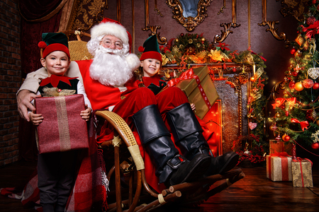 Santa Claus and the elves children with gift boxes. Miracles on Christmas. Stock Photo
