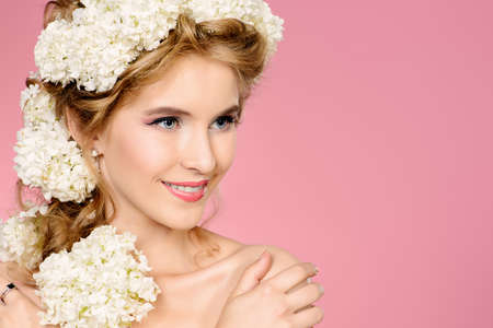 Beautiful young woman with natural make-up and wreath of white flowers on her head smiling at camera. Pink background. Summer, spring inspiration. Beauty, fashion, cosmetics. Stockfoto
