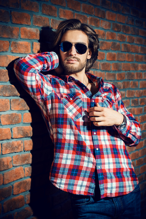 Handsome young man in sunglasses standing against the brick wall. Mens beauty, fashion. Mens barbershop, Hairstyle.