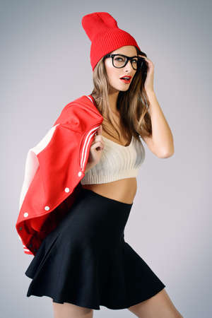 Fashion shot of a sexual girl with bright red lips wearing modern clothes. College style. Hipster. Youth fashion.