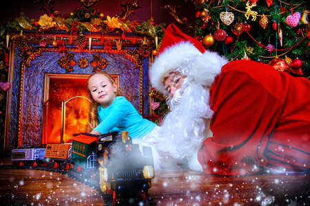 Good old Santa Claus playing with a child girl with toys under the Christmas tree. Christmas concept. Magic time. Stock Photo