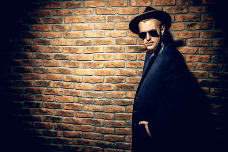 Portrait of a stylish handsome man wearing hat, coat and sunglasses. Men's beauty, seasonal fashion. Brick wall background.