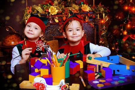 Little fairy elves make gifts for children at Christmas. Workshop of Santa Claus. Christmas concept.