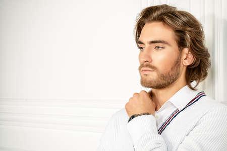 Attraktive junge Mann weißen Strickjacke posiert im luxuriösen Interieur trägt. Herren Schönheit, Mode-Modell. Haar Styling.