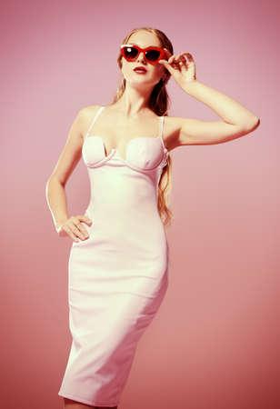 Bezaubernde junge Frau trägt elegante passendes Kleid und Sonnenbrille posiert auf rosa Hintergrund. Schönheit, Mode-Konzept. Abendkleider Kollektion. Standard-Bild
