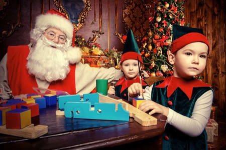 Santa Claus and the elves make gifts for children at Christmas. Workshop of Santa Claus. Christmas concept. 版權商用圖片