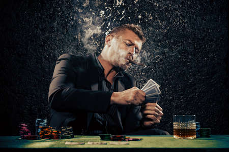 Rich gambler man with the cards and chips in casino. Gambling, playing cards and roulette. Reklamní fotografie