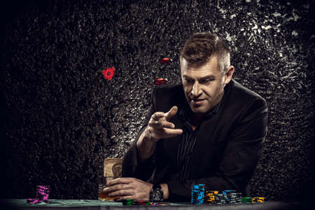 Excited gambling man throwing chips on a game table in a casino. Gambling, playing cards and roulette. Reklamní fotografie - 66630153
