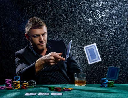 Uomo emozionante gioco d'azzardo gettando carte da gioco su un tavolo da gioco in un casinò. Il gioco d'azzardo, carte da gioco e roulette. Archivio Fotografico - 66629388