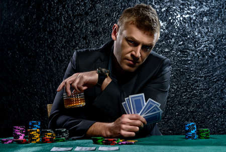 A wealthy mature man drinking brandy and playing poker with the excitement in a casino. Gambling, playing cards and roulette. Banque d'images