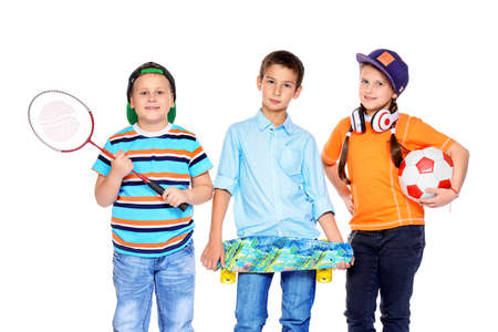 Sports and activities for children. Group of happy boys and a girl posing at studio. Education. Isolated over white background.