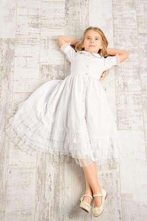 Beautiful little girl in white dress. Kid's fashion.