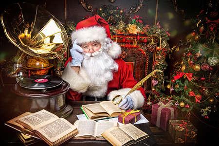 Dobry stary Mikołaj czytanie książek i słuchanie starego gramofonu w domu. Świąteczne piosenki. Koncepcja Boże Narodzenie.
