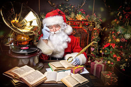 Good old Santa Claus reading a book and listening to old gramophone at home. Christmas songs. Christmas concept. Reklamní fotografie - 66923098