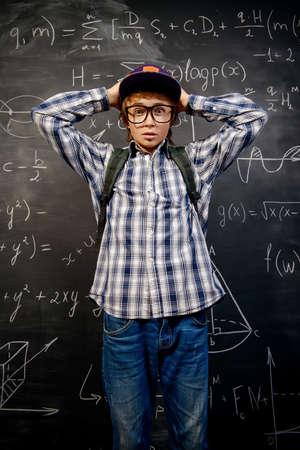 教育、高校、大学。学校の黒板に立って面白い感情的な学生少年の肖像画。 写真素材