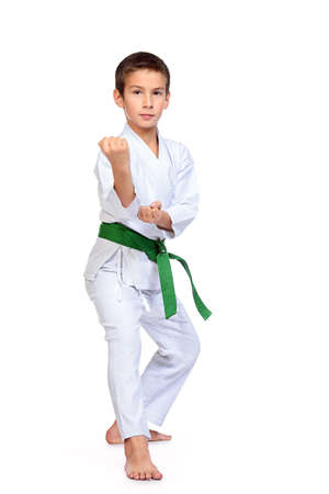 Karate boy in kimono posing in the studio. Sport, martial arts. Isolated over white. Full length portrait. Banque d'images