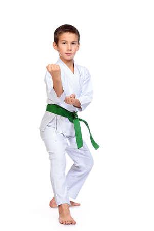 Karate boy in kimono posing in the studio. Sport, martial arts. Isolated over white. Full length portrait. Archivio Fotografico