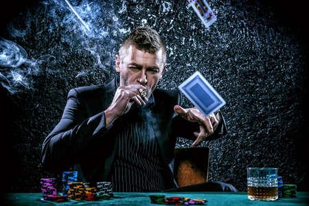 Excited Glücksspiel Mann in einem Casino-Spielkarten auf einem Spieltisch zu werfen. Glücksspiel, Spielkarten und Roulette.