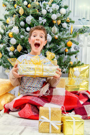 Funny boy in pajama expressing big surprise sitting near the Christmas tree and Christmas gifts. Time for miracles.