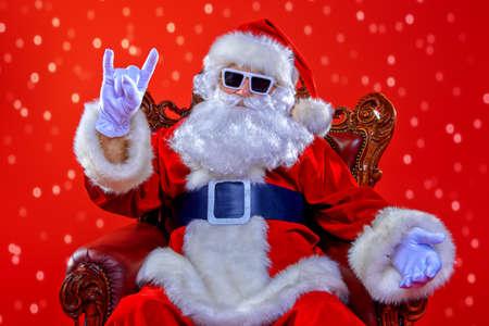 赤い背景の上のサングラスで現代のサンタ クロースをクールします。クリスマスのコンセプトです。 写真素材