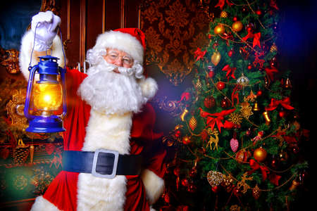 Christmas concept. Portrait of a fairytale Santa Claus standing with lantern in a beautiful Christmas room. Time of miracles. Stock Photo