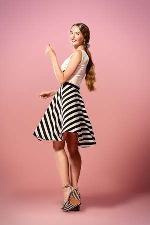 Beautiful happy young woman wearing skirt and top blouse alluring over pink background. Fashion studio shot. Full length portrait.