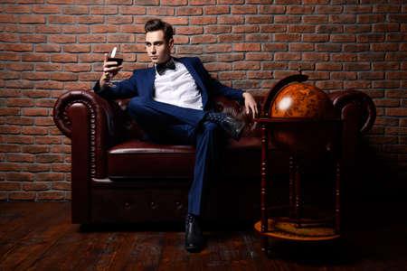 Het opleggen van goed geklede man in een luxe appartementen met een klassiek interieur. Luxe. Men's beauty, fashion. Stockfoto - 67990363
