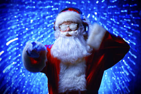 DJ Santa Claus in snowy glasses and headphones. Christmas songs and music. Disco lights in the background. Reklamní fotografie