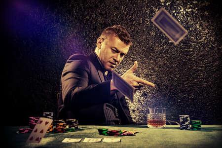 Excité jeu homme lancer des cartes à jouer sur une table de jeu dans un casino. Le jeu, cartes à jouer et la roulette.