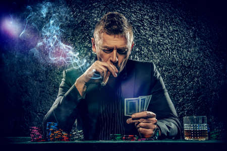 Rich gambler man with the cards and chips in casino. Gambling, playing cards and roulette. Archivio Fotografico