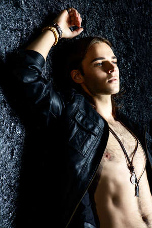 Fashion schot. Knappe seksuele jonge man in leren jas onthulling van zijn borst. Men's schoonheid.