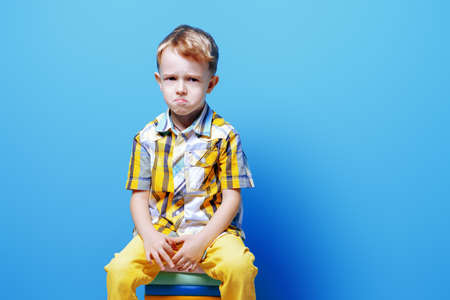 Portrait of a little sad boy. Bright background. Kid's fashion. Stock Photo