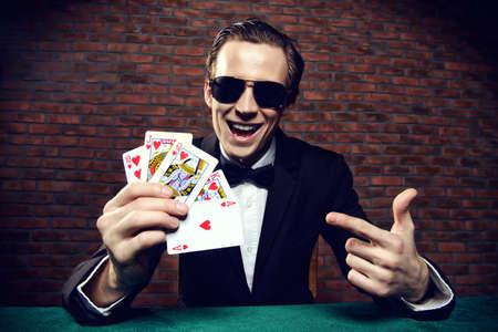Un uomo fortunato ricco carte da gioco con l'emozione in un casinò. Il gioco d'azzardo, carte da gioco e roulette.
