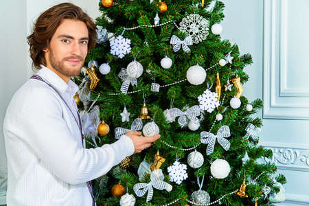 Christmas concept, male fashion. Handsome young man in elegant cardigan posing in luxurious apartments decorated for Christmas. Hairstyle. Stock Photo