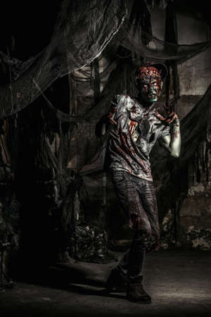 Terrible bloody zombie man  with the brains out in search of his victim. Horror. Halloween concept. Stock Photo
