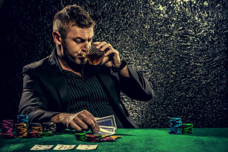 A wealthy mature man drinking brandy and playing poker with the excitement in a casino. Gambling, playing cards and roulette. Reklamní fotografie