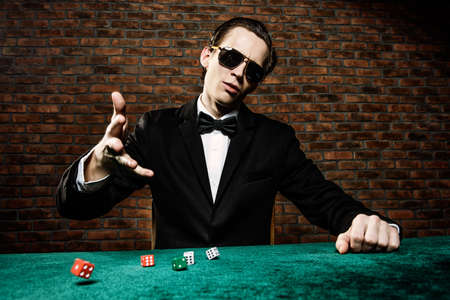 Excited gambling man throwing dice on a game table in a casino. Gambling, playing cards and roulette. Reklamní fotografie - 69602553