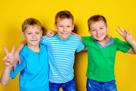 Three boys best friends standing together. Bright yellow background. Summer fashion.