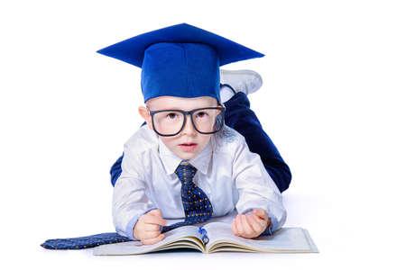 Quattro anni ragazzo in camicia bianca, un grande cravatta, cappello accademico e grandi occhiali sdraiato su un pavimento con un libro. concetto educativo.