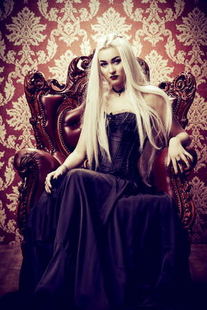 halloween gothic style beautiful young woman with long blonde hair and black make up wearing