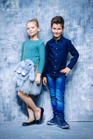 Kid's fashion. Two modern children posing together at studio. Clothes for children. Easter holidays.