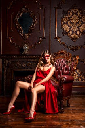 Charmante elegante vrouw in een prachtige rode jurk en maskerademasker zit in een stoel in een luxe appartement. Klassiek vintage interieur. Beauty, fashion.