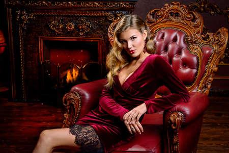 美しいベルベットのドレスでゴージャスなエレガントな女性は、高級マンションで椅子に座っています。クラシックなビンテージ インテリア。美容