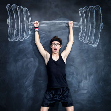 Funny skinny guy raises huge heavy barbell, drawn on a blackboard. Sports and health concept.