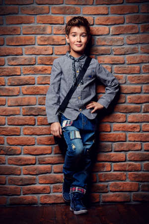 Kids fashion. Modern nine year old boy posing at studio over brick wall background. Clothes and accessories for children.